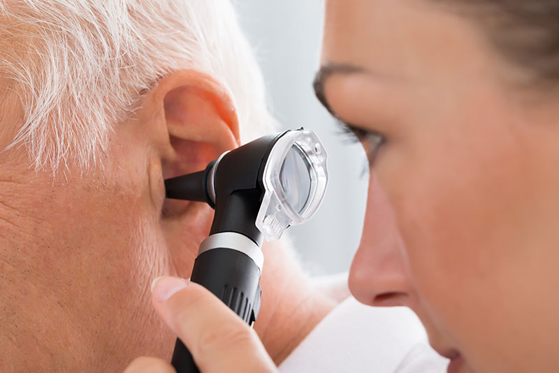 female audiologist checking up ear for wax removal